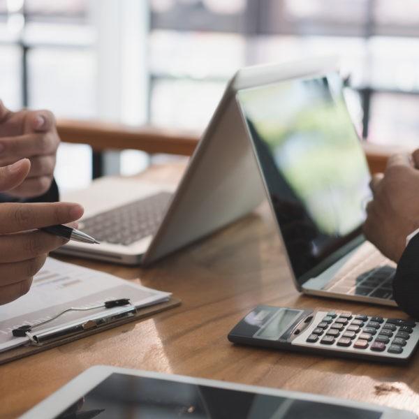 dwie osoby siedzace przy laptopach