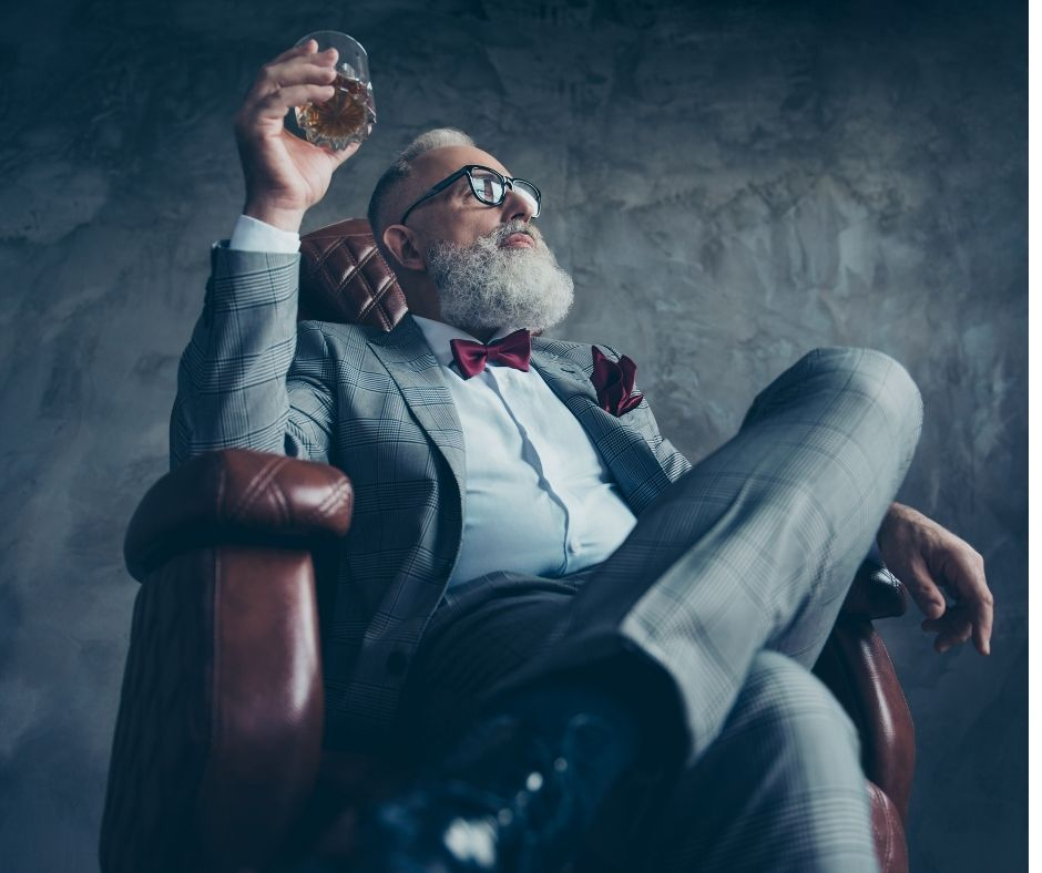 mężczyzna w garniturze z whisky w ręku