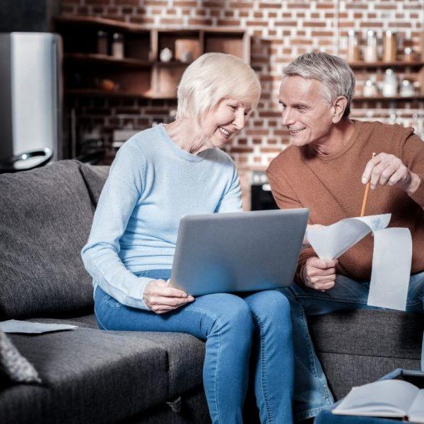 dwoje starszych ludzi siedzących na sofie z laptopem w ręku